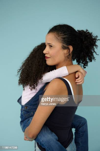 happy mother carrying daughter against light blue background - nerys jones stock photos and pictures