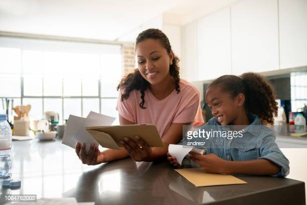 happy mother checking the mail at home with her daughter - mail stock pictures, royalty-free photos & images