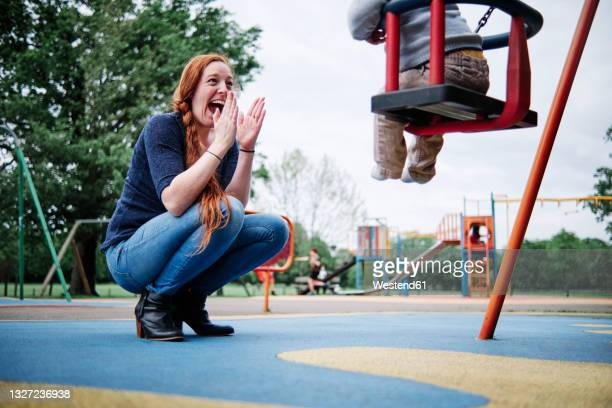 happy mother clapping while crouching near son sitting on swing in playground - parent stock pictures, royalty-free photos & images