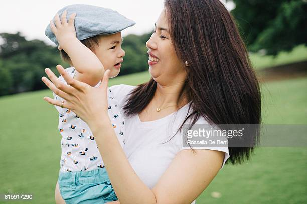 Happy mother comforting her crying son outdoors in a park