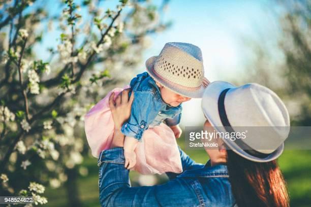 果樹園での赤ちゃんの娘と踊る幸せな母