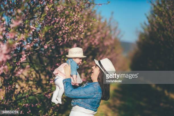 Glückliche Mutter mit Tochter im Obstgarten zu tanzen