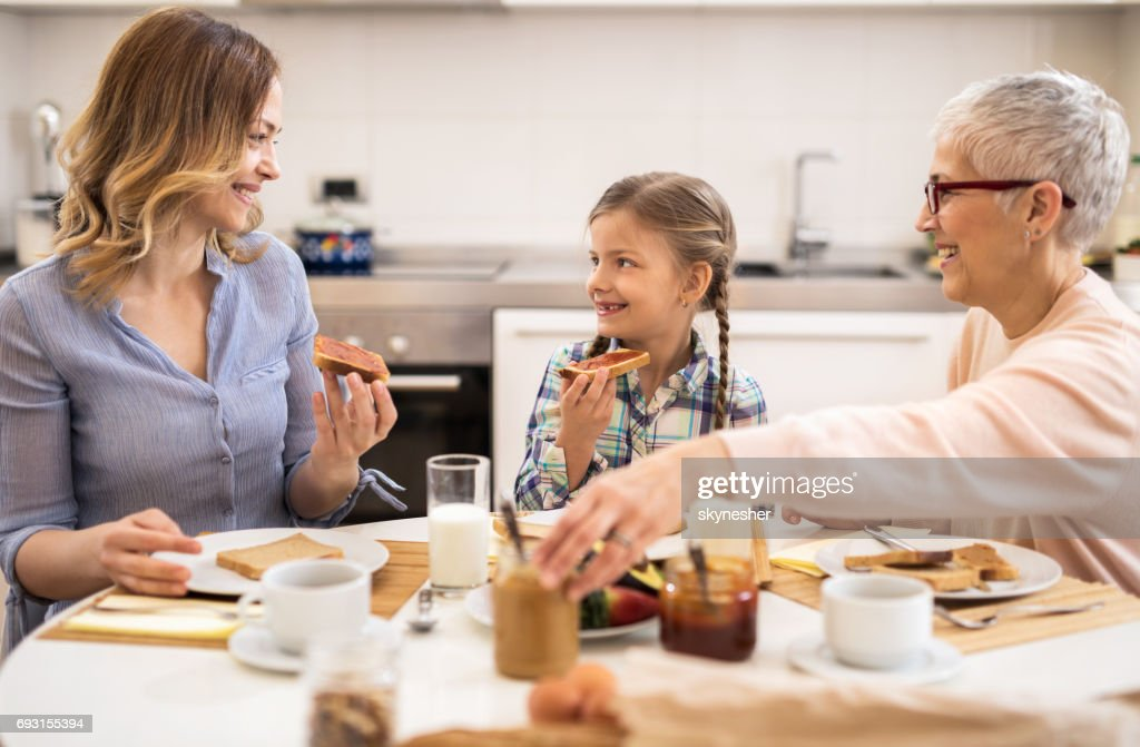 Happy mother, daughter and grandmother communicating during breakfast in the kitchen. : Stock Photo