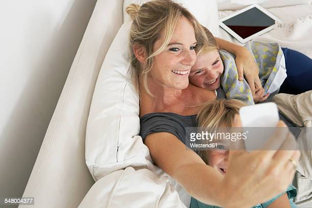 Happy mother, daughter and son on couch taking a selfie