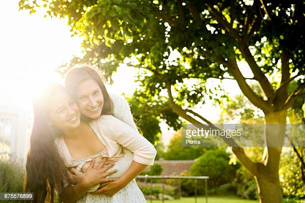 Happy mother embracing daughter in yard
