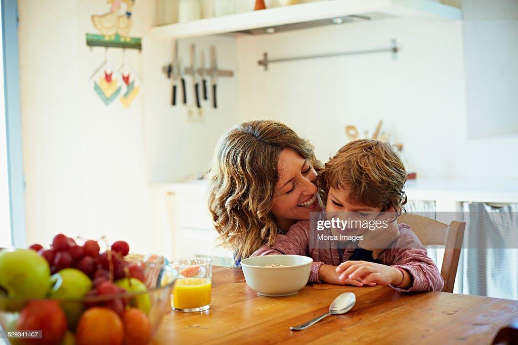 Happy mother embracing son having breakfast : Stock Photo
