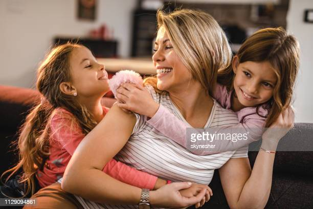 happy mother enjoying in a hug by her two little daughters at home. - twin stock pictures, royalty-free photos & images