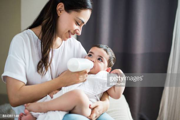 happy mother feeding baby with bottle at home - baby bottle stock pictures, royalty-free photos & images
