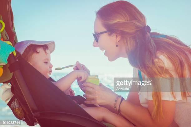 Happy mother feeding her baby boy on the beach
