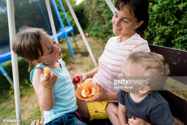 Happy mother feeding her children with fresh fruits
