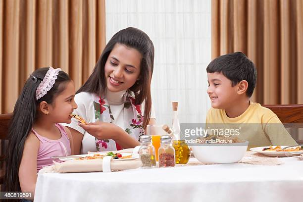 Happy mother feeding pizza to daughter with son sitting besides in restaurant