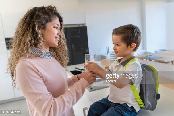 happy mother giving her son a snack after school - milk stock pictures, royalty-free photos & images