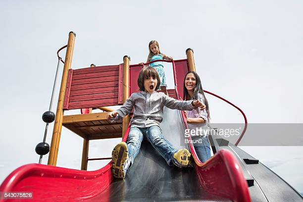 happy mother having fun with her children on a playground. - slide play equipment stock pictures, royalty-free photos & images