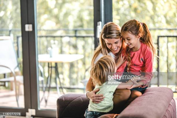 happy mother having fun with her son and daughter at home. - family with two children stock pictures, royalty-free photos & images