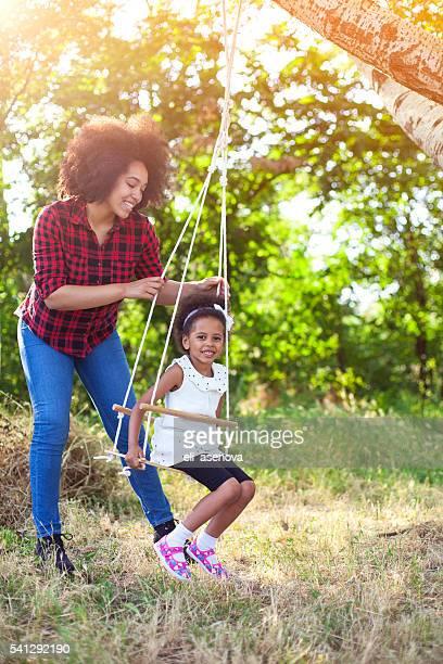 Glückliche Mutter mit Ihrem Kind Spaß haben auf einer Schaukel
