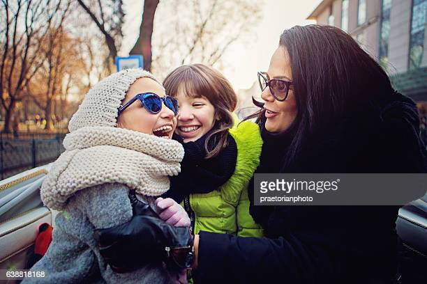 Happy mother is hugging her daughters in horse carriage
