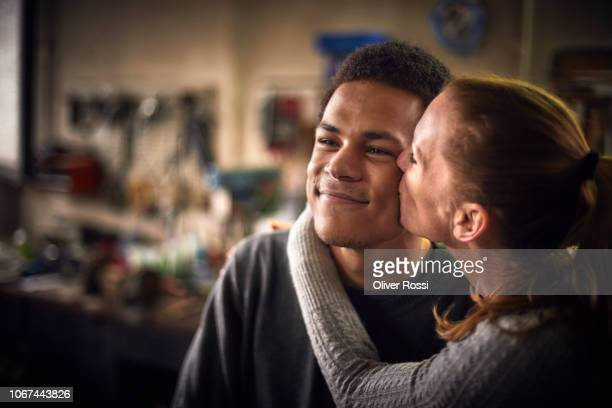 happy mother kissing son in a workshop - 息子 ストックフォトと画像