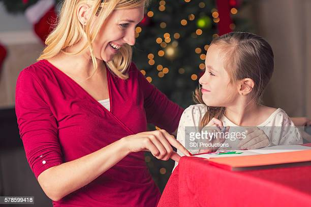 Happy mother laughing with her daughter while writing Christmas cards