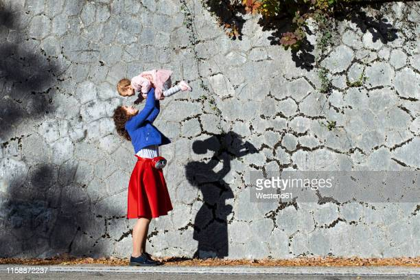 happy mother lifting up little daughter at a - holding aloft stock pictures, royalty-free photos & images