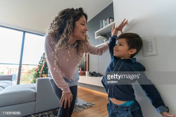 happy mother measuring her son at home - high up stock pictures, royalty-free photos & images