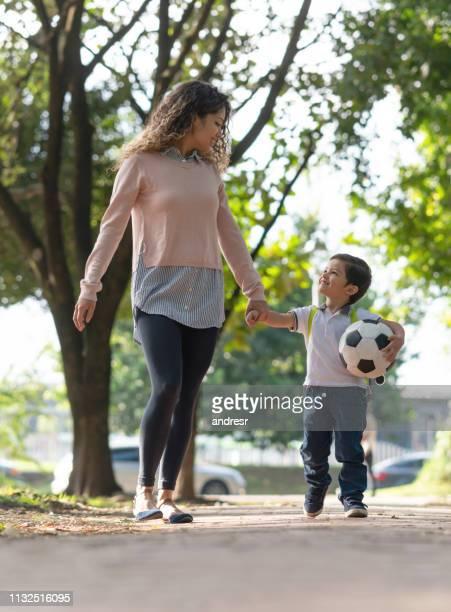 madre feliz recogiendo a su hijo de la escuela - mama futbol fotografías e imágenes de stock