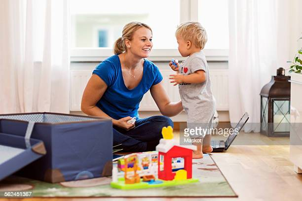 Happy mother playing with baby boy at home