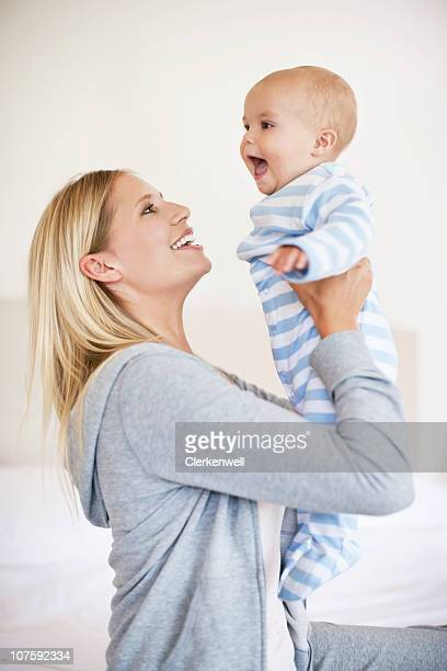 Happy mother playing with baby son (6-11 months)