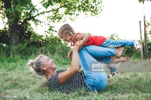 happy mother playing with daughter on meadow - familie mit einem kind stock-fotos und bilder
