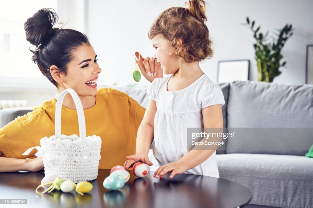 Happy mother playing with her child with Easter eggs : Stock Photo