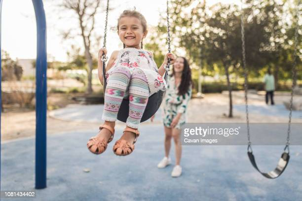 happy mother pushing cute daughter swinging at playground - swinging stock pictures, royalty-free photos & images