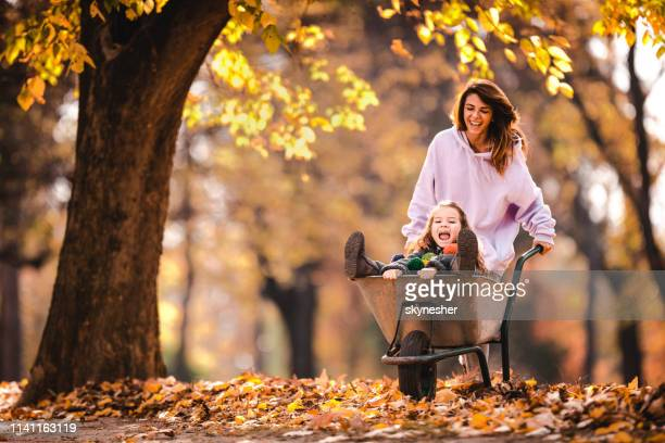 happy mother pushing her small daughter in a wheelbarrow at the park. - wheelbarrow stock pictures, royalty-free photos & images