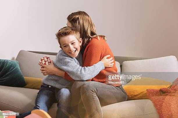 happy mother receiving christmas gift from her son - giving stock pictures, royalty-free photos & images