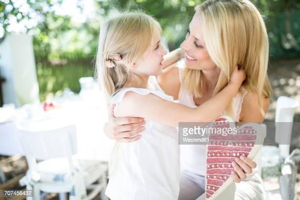 happy mother receiving heart form her daughter - muttertag stock-fotos und bilder