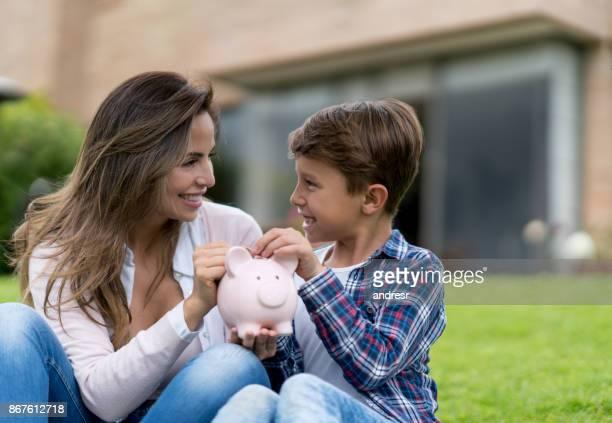 Glückliche Mutter mit ihrem Sohn Geld sparen