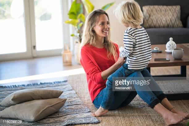 happy mother sitting on the floor at home playing with her son - adulto de mediana edad fotografías e imágenes de stock