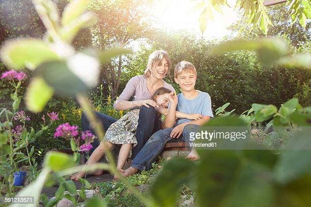 Happy mother, son and daughter in garden