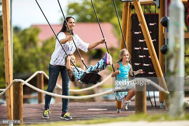 Happy mother swinging her two daughters at the playground.