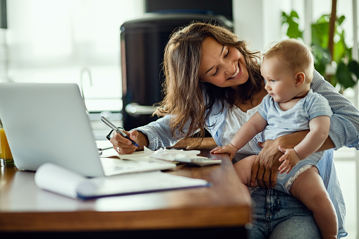 Happy mother talking to her baby while working at home. 1182823932