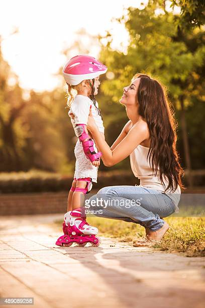 Happy mother talking to her small daughter in the park.