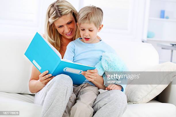 Happy mother teaches son to read, sitting on the sofa.
