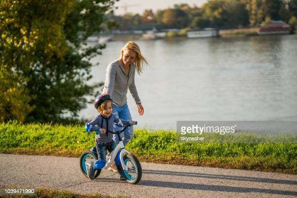 happy mother teaching her son how to ride a bicycle by riverside. - padding stock pictures, royalty-free photos & images