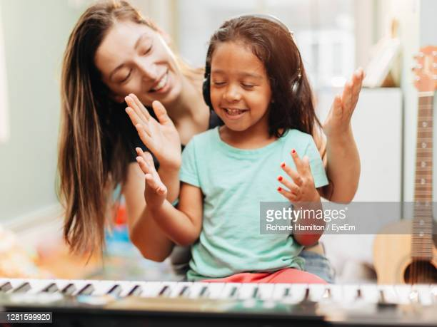 happy mother teaching piano to daughter at home - hamiltonmusical stockfoto's en -beelden