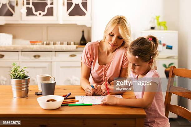 Happy mother watching her daughter drawing on the paper.