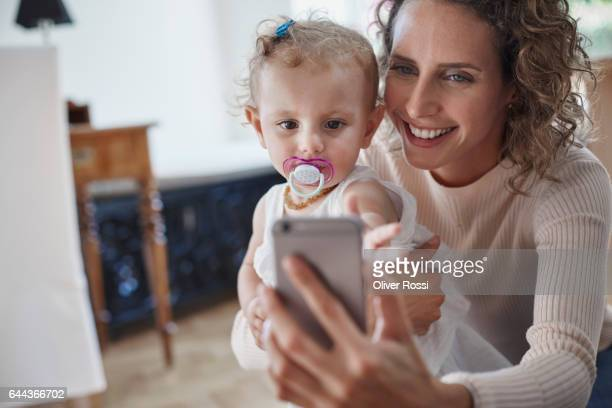 Happy mother with baby girl taking a selfie at home