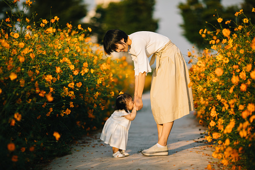 Happy mother with baby in yellow cosmos flower field - gettyimageskorea