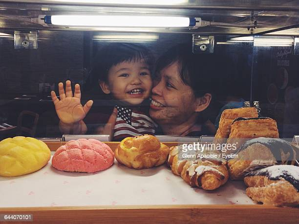 Happy Mother With Child Seen Through Glass At Bakery