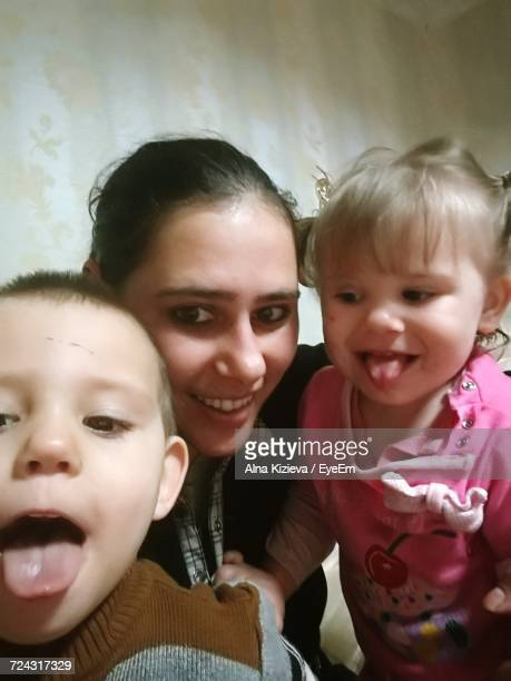 Happy Mother With Children Against Wall