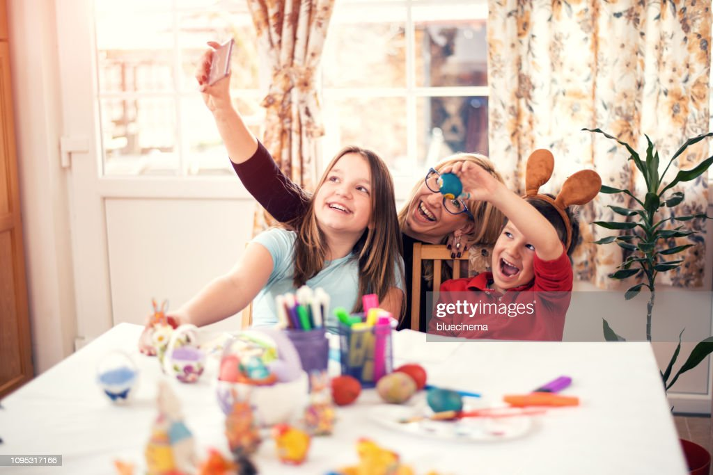 Happy mother with children painting Easter eggs at home : Stock Photo