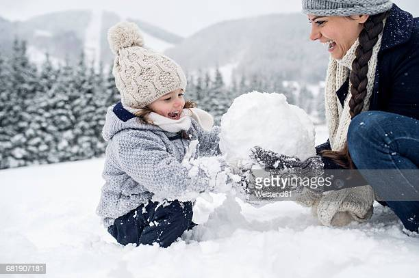 Happy mother with daughter building snowman