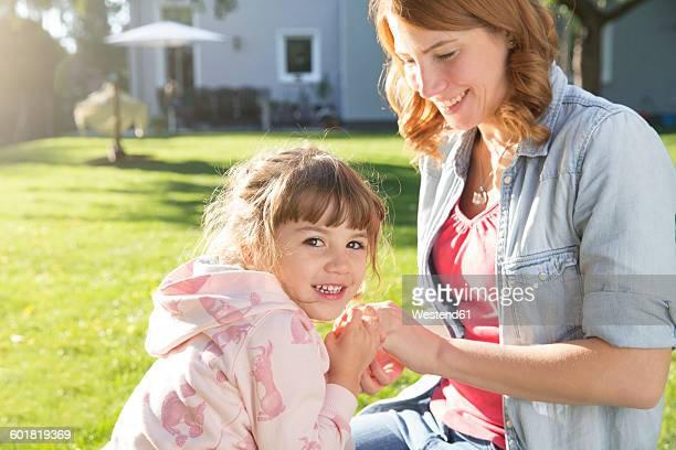 Happy mother with daughter in garden